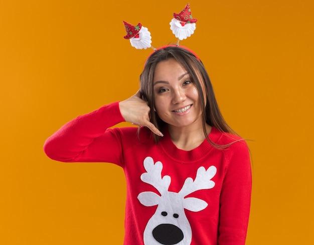 Glimlachend jong aziatisch meisje dat de hoepel van het kerstmishaar met sweater draagt die telefoongesprekgebaar toont dat op oranje muur wordt geïsoleerd Gratis Foto