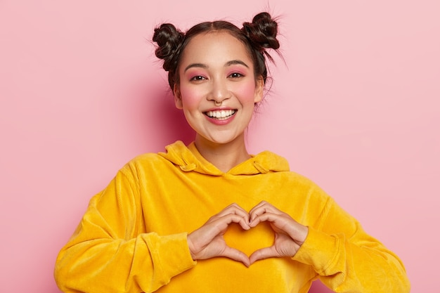 Glimlachend jong brunette meisje bekent ware gevoelens, maakt hartgebaar, gekleed in gele hoody, toont hartgebaar Gratis Foto