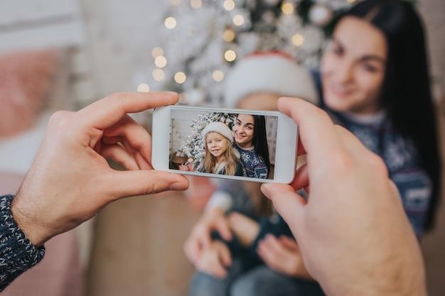 Glimlachend jong gezin in kerstsfeer foto maken met smartphone. Premium Foto