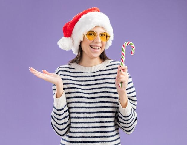 Glimlachend jong kaukasisch meisje in zonnebril met kerstmuts houdt riet van het suikergoed en houdt de hand open Gratis Foto