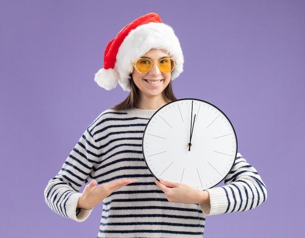 Glimlachend jong kaukasisch meisje in zonnebril met santahoed die en op klok met hand houden richt Gratis Foto