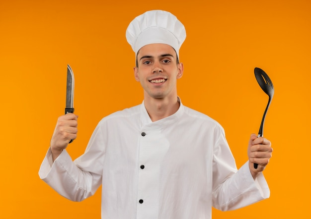 Glimlachend jong mannetje koel dragend mes en pollepel van de chef-kok eenvormig bedrijf Gratis Foto
