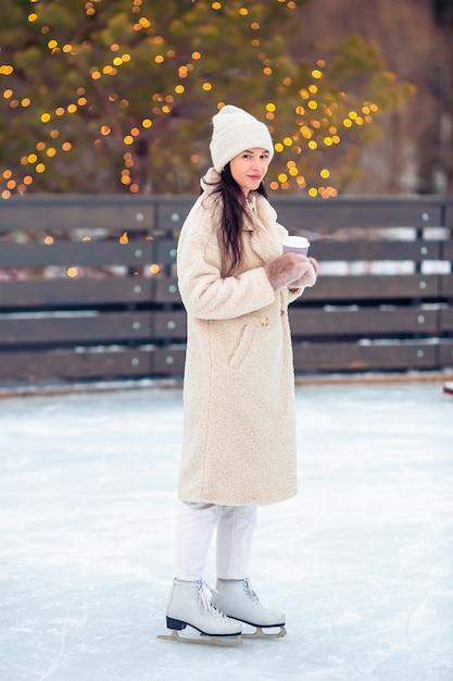 Glimlachend jong meisje die op ijsbaan in openlucht schaatsen Premium Foto