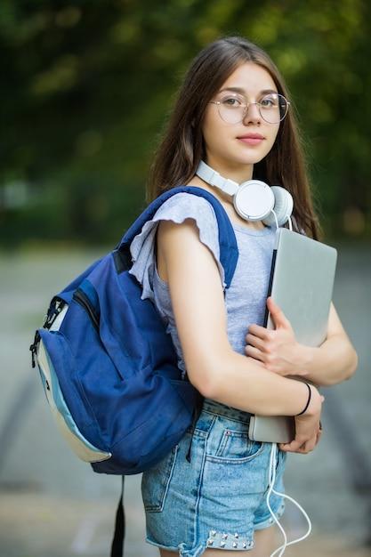 Glimlachend jong meisje student met rugzak mobiele telefoon te houden, wandelen in het park, luisteren naar muziek met koptelefoon Gratis Foto