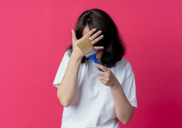 Glimlachend jong mooi de kwast van de meisjesholding en het verbergen van gezicht achter hand Gratis Foto