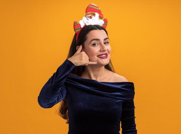 Glimlachend jong mooi meisje dragen blauwe jurk en kerst haar hoepel bedrijf speelgoed tonen telefoongesprek gebaar geïsoleerd op een oranje achtergrond Gratis Foto