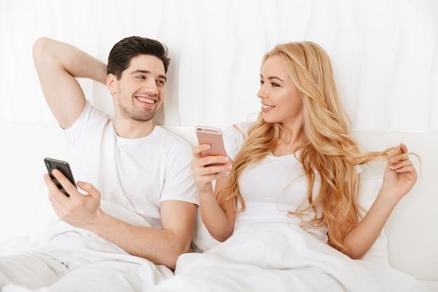 Glimlachend jong paar dat mobiele telefoons met behulp van Premium Foto