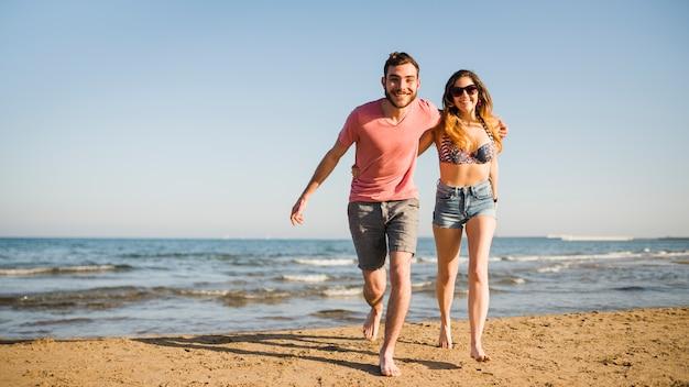 Glimlachend jong paar die samen op strand lopen Gratis Foto