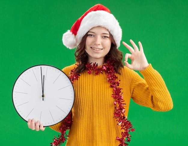 Glimlachend jong slavisch meisje met kerstmuts en met slinger rond de nek met klok en gebaren ok teken geïsoleerd op groene achtergrond met kopie ruimte Gratis Foto