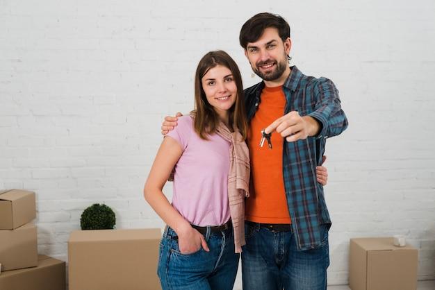 Glimlachend jong stel met huissleutels in hun nieuwe huis Gratis Foto