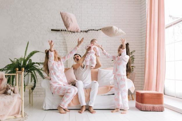 Glimlachend jonge ouders, hun twee dochters hebben thuis plezier en gooien kussens in een licht interieur Premium Foto