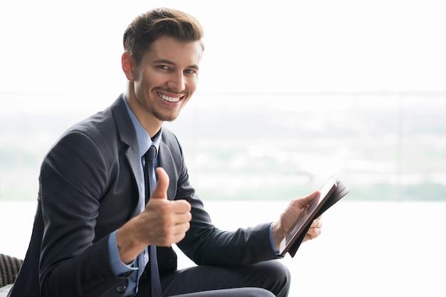 Glimlachend jonge zakenman met duim omhoog en tablet Gratis Foto