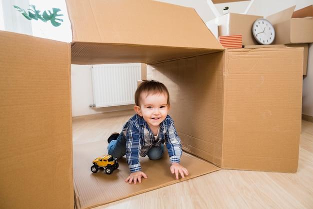 Glimlachend jongetje spelen in de bewegende kartonnen doos met speelgoedauto Gratis Foto