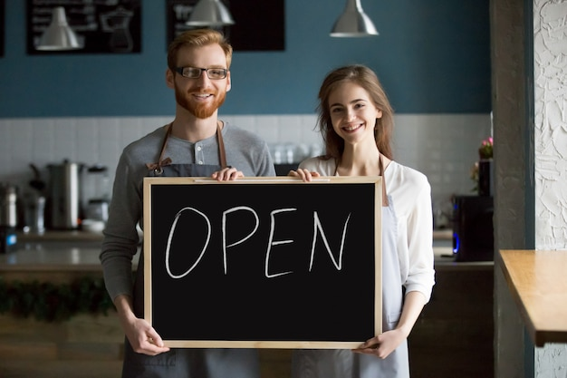 Glimlachend kelner en serveersterholdingsbord met open teken, portret Gratis Foto
