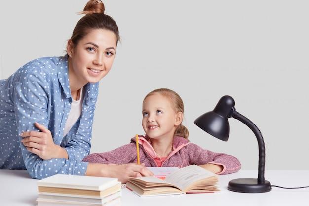 Glimlachend klein charmant meisje zit aan tafel, doet huiswerk samen met haar moeder, probeert compositie te schrijven, kijkt vreugdevol, gebruikt leeslamp voor goed zicht, geïsoleerd op witte muur Gratis Foto