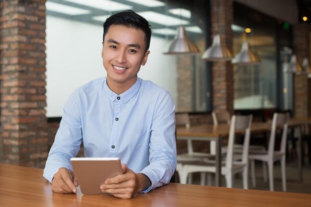 Glimlachend man zittend bij cafe tafel met tablet Gratis Foto