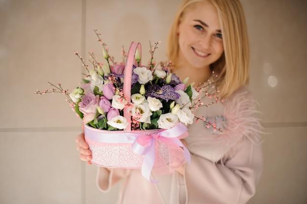 Glimlachend meisje dat een de lentemand van tedere witte en purpere bloemen houdt Premium Foto