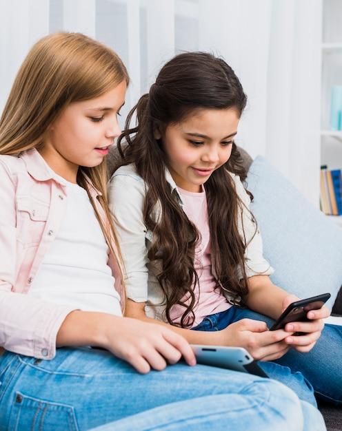 Glimlachend meisje dat haar vriend bekijkt die mobiele telefoon met behulp van Gratis Foto
