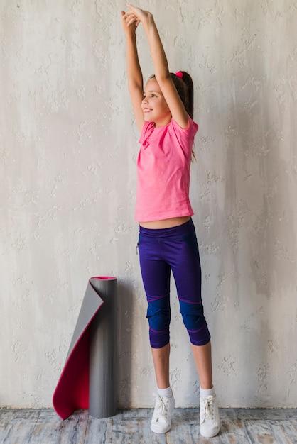 Glimlachend meisje dat zich voor concrete muur bevindt die zijn hand uitrekt Gratis Foto