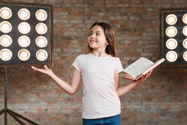 Glimlachend meisje die in studio repeteren die een open boek houden Gratis Foto