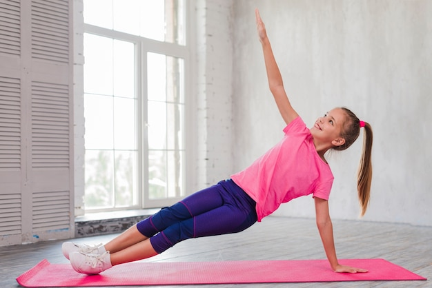 Glimlachend meisje die uitrekkende oefening in de gymnastiek doen Gratis Foto