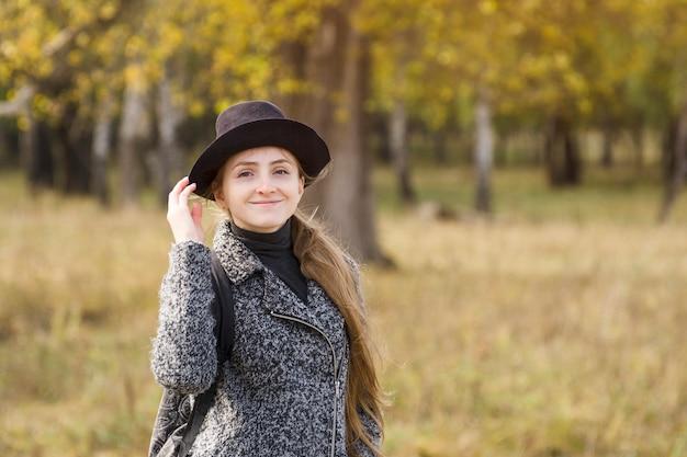 Glimlachend meisje in een hoed die zich in het de herfstbos bevindt. Premium Foto