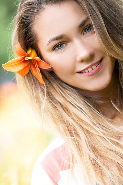 Glimlachend meisje met leliebloem in haar Gratis Foto