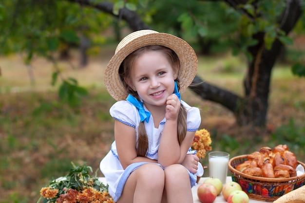 Glimlachend meisje met twee vlechten op haar hoofd en in strohoed op picknick in de tuin. zomervakantie. Premium Foto