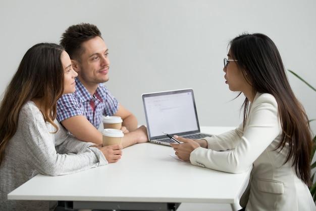 Glimlachend millennial paar die aan aziatische adviseursadvocaat raadplegen die klanten raadplegen Gratis Foto