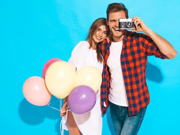Glimlachend mooi meisje en haar knappe vriendje bedrijf bos van kleurrijke ballonnen. gelukkig paar die foto van zich op retro camera nemen. fijne verjaardag Gratis Foto