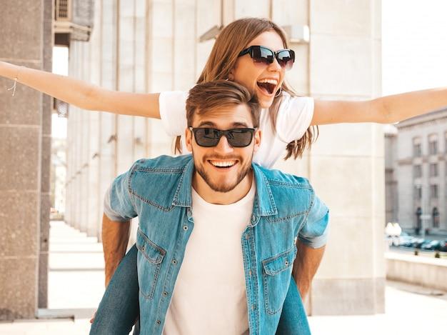 Glimlachend mooi meisje en haar knappe vriendje in casual zomer kleding. man die zijn vriendin op de rug draagt en zij die haar handen opheft. Gratis Foto