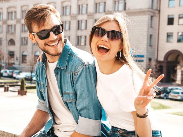 Glimlachend mooi meisje en haar knappe vriendje in casual zomer kleding. . vredesteken tonen Gratis Foto