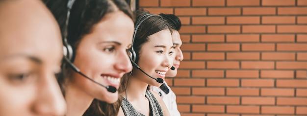 Glimlachend multi-etnisch telemarketing klantenserviceteam dat in call centre werkt Premium Foto