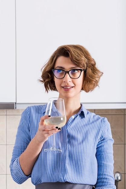 Glimlachend overwogen jonge wijnglas van de vrouwenholding ter beschikking Gratis Foto