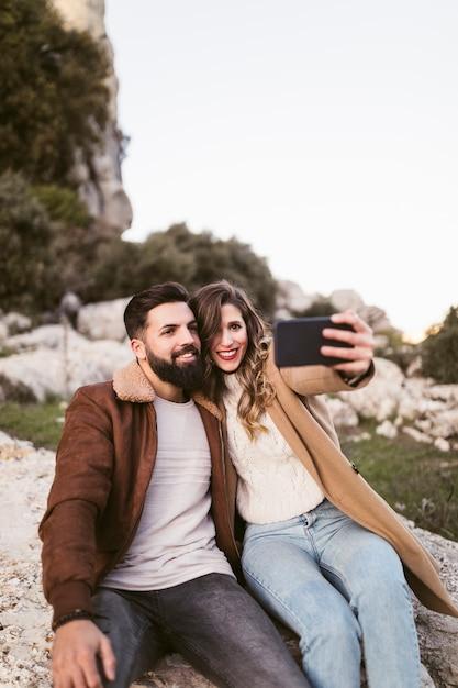 Glimlachend paar die een selfie op een rots nemen Gratis Foto