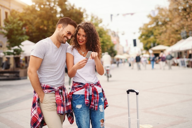 Glimlachend paar die foto's op slimme telefoon bekijken terwijl status op straat. reizend concept. Premium Foto