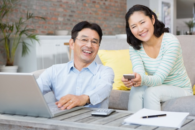 Glimlachend paar die laptop en smartphone in de woonkamer met behulp van Premium Foto