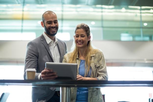 Glimlachend paar met behulp van digitale tablet in wachtruimte Gratis Foto