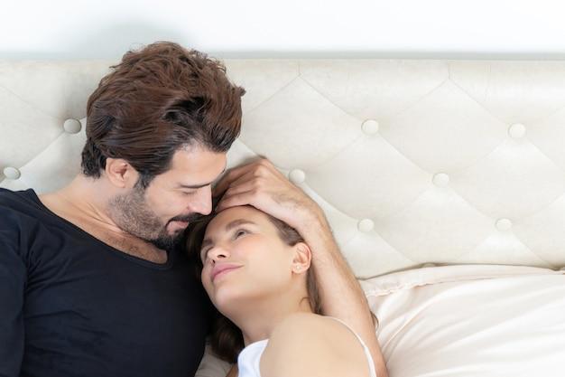 Glimlachend paar ontspannen en paren knuffelen in bed Gratis Foto