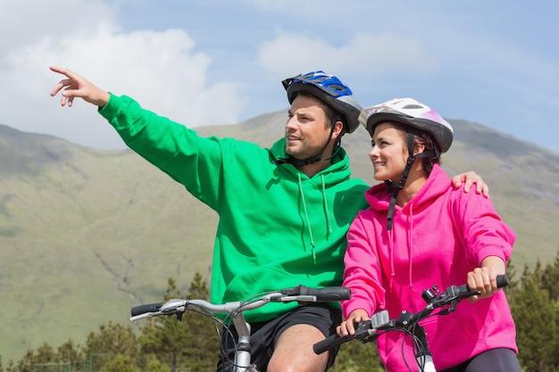 Glimlachend paar op een fietsrit die verbindingsdraden met een kap met mens het richten dragen Premium Foto