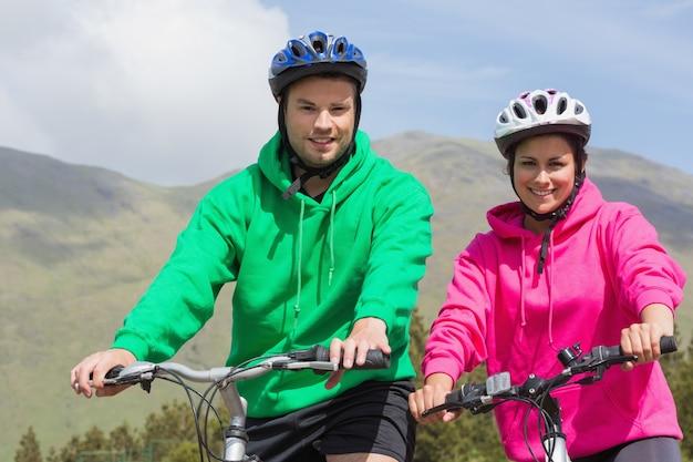 Glimlachend paar op een fietstocht dragen hooded jumpers Premium Foto