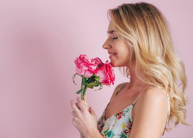 Glimlachend portret van de holdingsrozen van de blonde jonge vrouw ter beschikking tegen roze achtergrond Gratis Foto