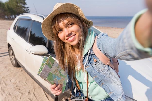 Glimlachend portret van de vrouwelijke kaart die van de reizigersholding ter beschikking selfie met haar auto op strand nemen Gratis Foto