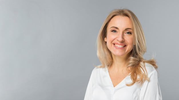 Glimlachend portret van een blonde jonge onderneemster die zich tegen grijze achtergrond bevindt Gratis Foto