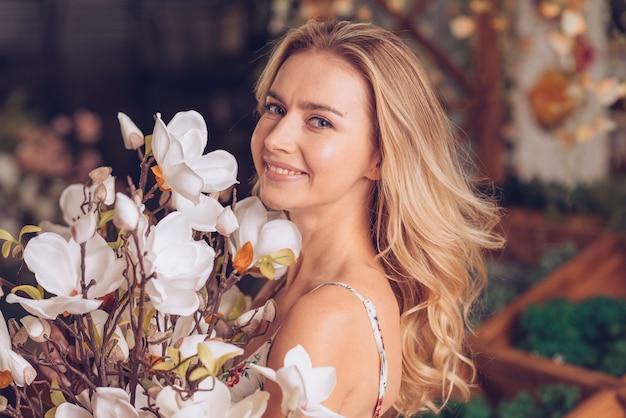 Glimlachend portret van een blonde jonge vrouw met witte mooie bloemen Gratis Foto