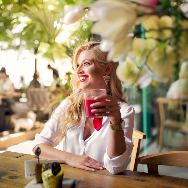 Glimlachend portret van een jong glas van de vrouwenholding sap in het restaurant Gratis Foto