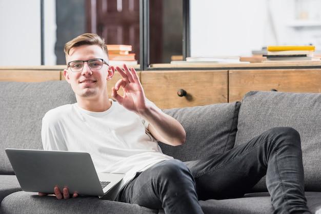 Glimlachend portret van een jonge mens die op laptop van de bankholding in hand liggend ok teken liggen Gratis Foto
