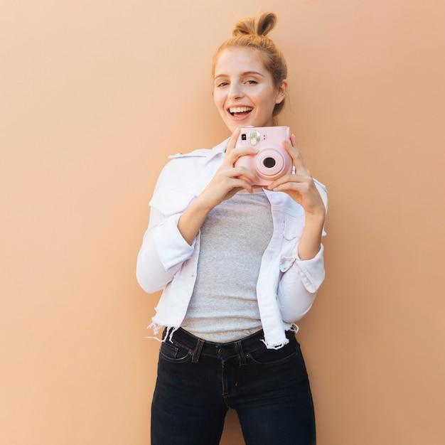 Glimlachend portret van een jonge mooie vrouw die roze onmiddellijke camera houdt tegen beige achtergrond Gratis Foto