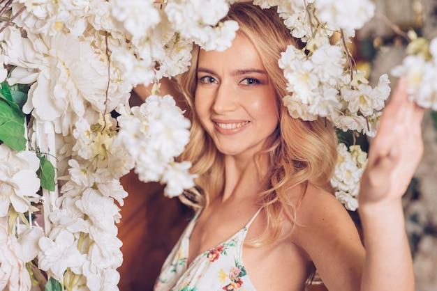 Glimlachend portret van een jonge vrouw onder de witte mooie bloemen Gratis Foto