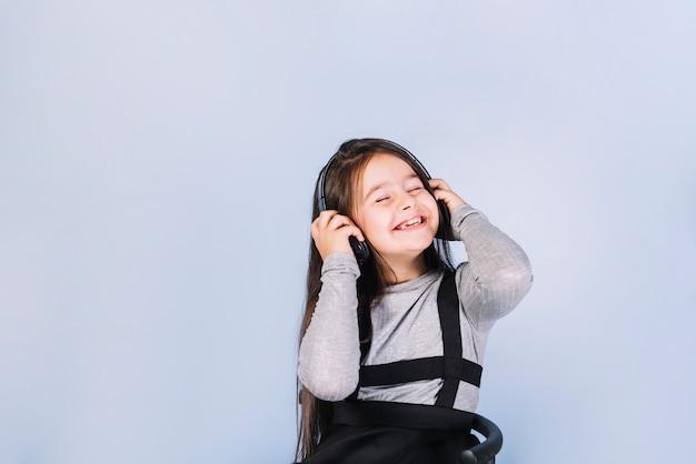 Glimlachend portret van een meisje die van de muziek op hoofdtelefoon genieten tegen blauwe achtergrond Gratis Foto